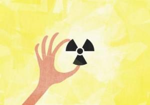 A hand holding a radioactive symbol
